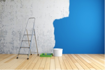 concrete wall being painted blue